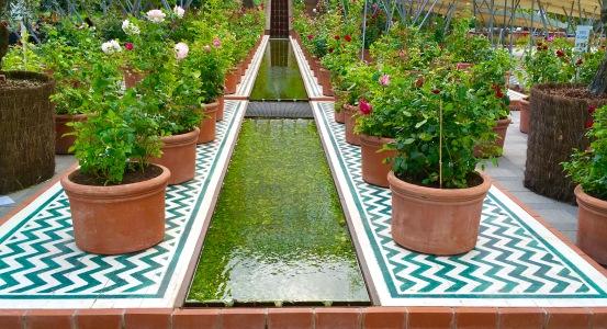 Pflanzen in Tongefäßen, Kacheln in Mustern und Wasser in sanfter Bewegung
